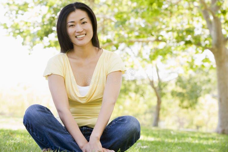 siedzieć na uśmiechniętym kobiety obrazy royalty free