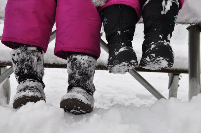 Siedzieć w ławce odpoczywa mimo to dzień bawić się na śniegu Zima jest zabawą fotografia stock