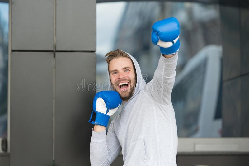 Sieger nimmt es aller Mann auf dem lächelnden Gesicht, das mit Boxhandschuhen als Sieger, städtischer Hintergrund aufwirft Sportl lizenzfreies stockbild