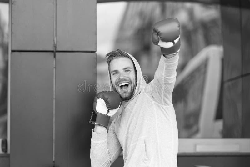 Sieger nimmt es aller Mann auf dem lächelnden Gesicht, das mit Boxhandschuhen als Sieger, städtischer Hintergrund aufwirft Sportl stockfoto