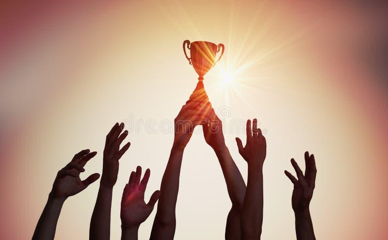 Siegermannschaft hält Trophäe in den Händen Schattenbilder vieler Hände im Sonnenuntergang stockfotos
