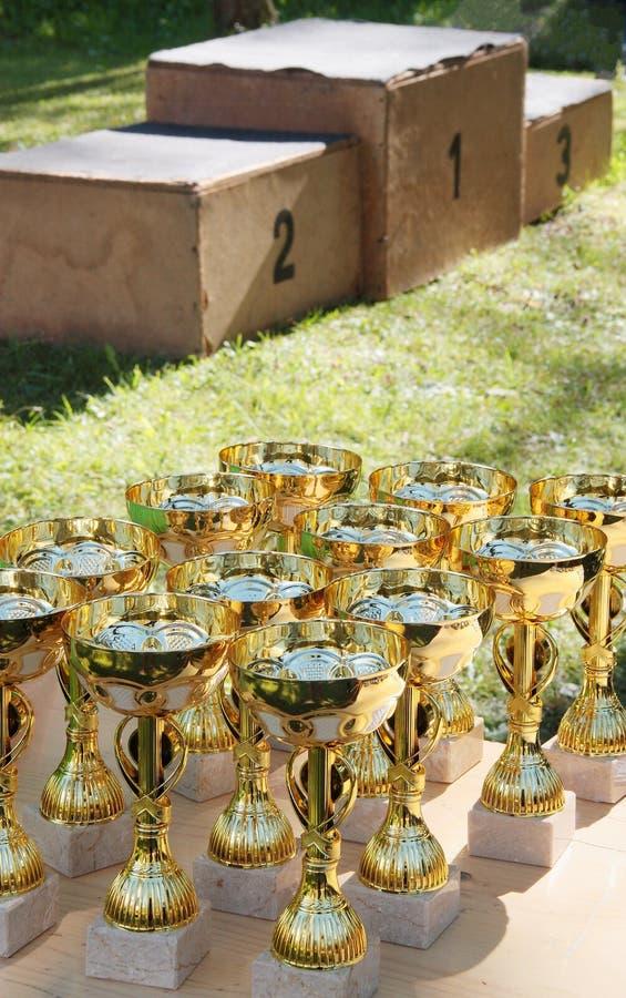 Siegerpodium und -Cups benutzt in den Kindersommerspielen stockfotografie