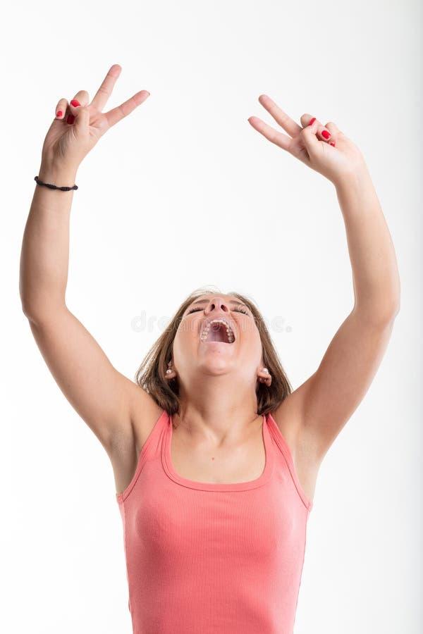 Siegreiche junge zujubelnde und lachende Frau stockfotografie