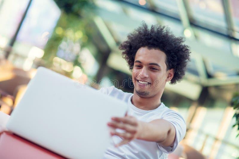 Siegreicher gut aussehender Mann, der seinen Laptop beim Sitzen im hellen Wohnzimmer betrachtet lizenzfreie stockbilder