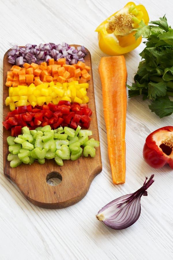 Siekający świezi warzywa marchewki, seler, cebula, barwiący pieprze układali na tnącej desce na białej drewnianej powierzchni, ni fotografia stock