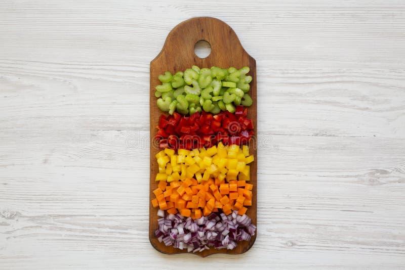 Siekający świezi warzywa marchewki, seler, czerwona cebula, barwiący pieprze układali na tnącej desce na białym drewnianym stole  zdjęcia royalty free