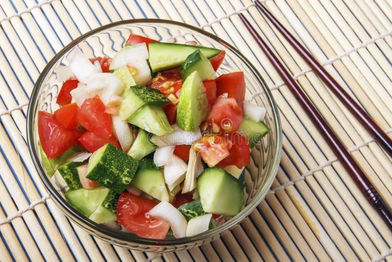 Siekający warzywa - ogórki, pomidory i cebule w, szklanym pucharze i chopstick na bambusie matują na widok kosmos kopii fotografia royalty free