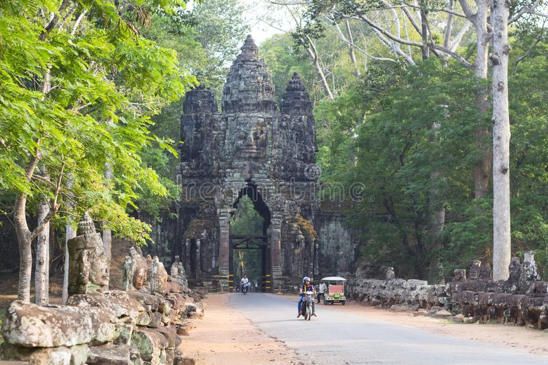 Siem Przeprowadza żniwa, Kambodża - 26 Marzec 2018: Angkor Thom brama z statuami i motocykli/lów jeźdzami obraz stock