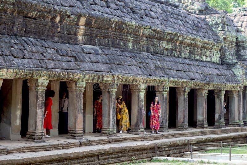Siem Przeprowadza żniwa, Kambodża - 27 Marzec 2018: Chiński turysta w Angkor Wat kompleksie Młode kobiety w sukniach robi fotogra obraz stock
