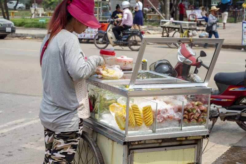 Siem Przeprowadza żniwa, Kambodża - 26 Marzec, 2018: Młoda kobieta bubla owoc od wisząca ozdoba stojaka Uliczny karmowy sprzedawc obrazy royalty free