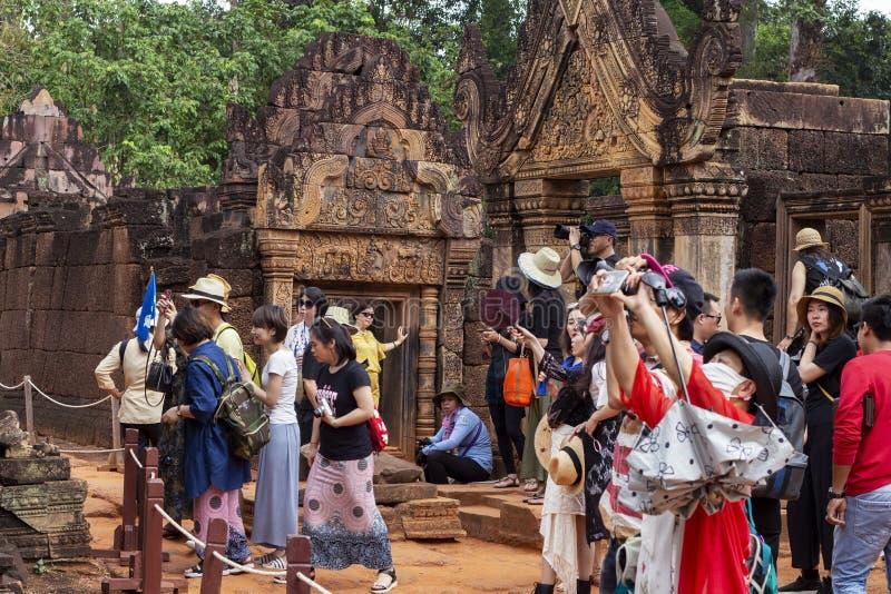 Siem Przeprowadza żniwa, Kambodża - 29 Marzec 2018: turyści w angkorian świątynnym Banteay Srei Azjatyccy turyści z smartphone ka obraz stock
