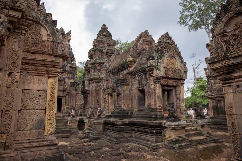 Siem Przeprowadza żniwa, Kambodża - 29 Marzec 2018: turyści w angkorian świątynnym Banteay Srei Kamień rzeźbiący wystrój na hindu obraz stock