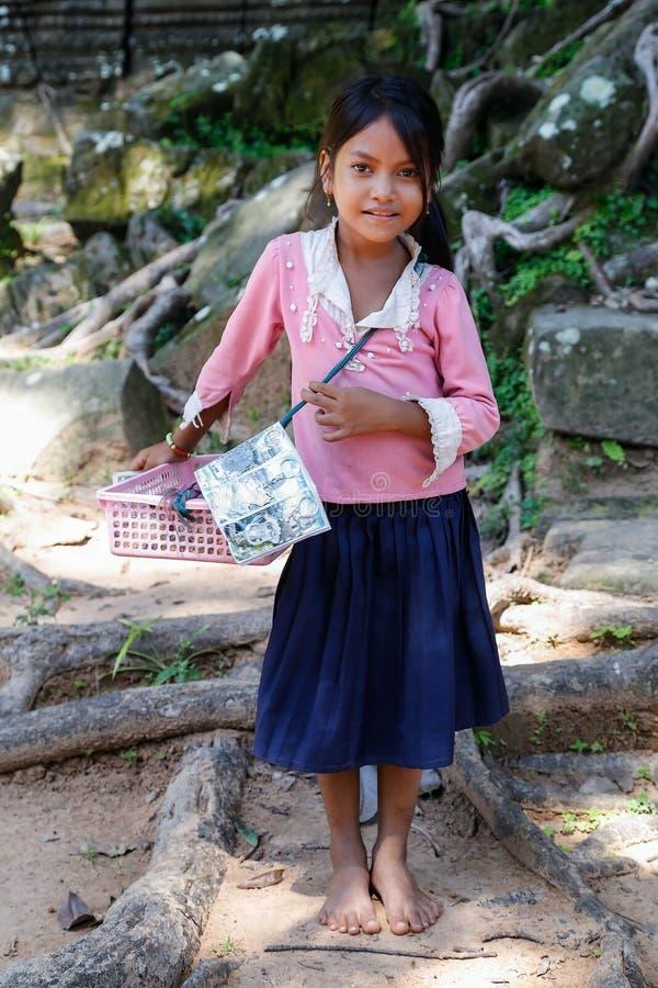 SIEM REAP ANGKOR WAT /CAMBODIA - CIRCA AUGUSTI 2015: Unga flickan säljer souvenir till den Angkor Wat för turister förutom temple royaltyfria bilder