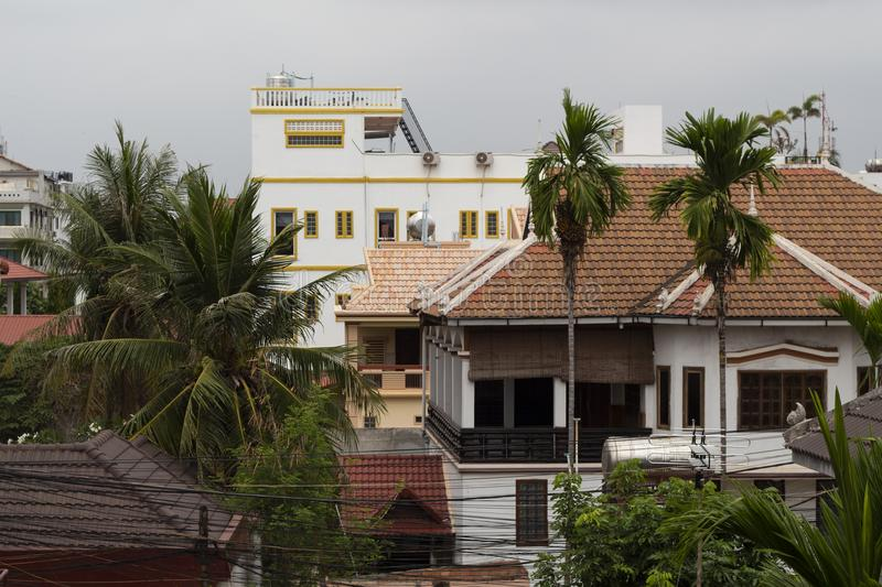 Siem Reap buildings panorama with tile roof top and palm trees. Rooftop view to cambodian city. Modern cityscape in South Asia. Tourist infrastructure hotel stock images