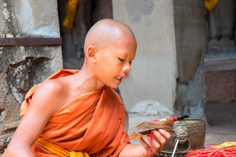 Siem Reap, Cambodge - avril, 13,2018 : Le jeune moine lit des incantations Moine bouddhiste de prière photographie stock libre de droits
