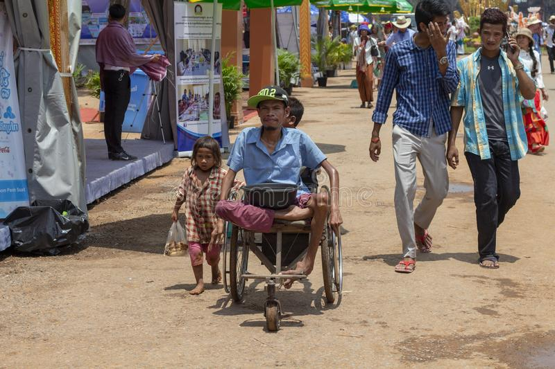 Siem Reap, Cambodia, 14 April 2018: Poor children and disabled beggar in chair on public market street. stock photo