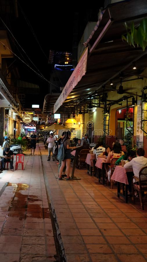 People eat dinner at a cafe outside, night time royalty free stock image