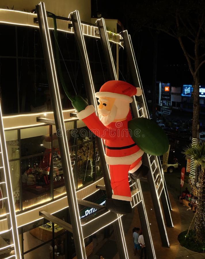 Santa Claus is climbing the wall of a shopping center. Christmas decor. Siem Reap, Cambodia, December 23, 2018 Santa Claus is climbing the wall of a shopping royalty free stock photography