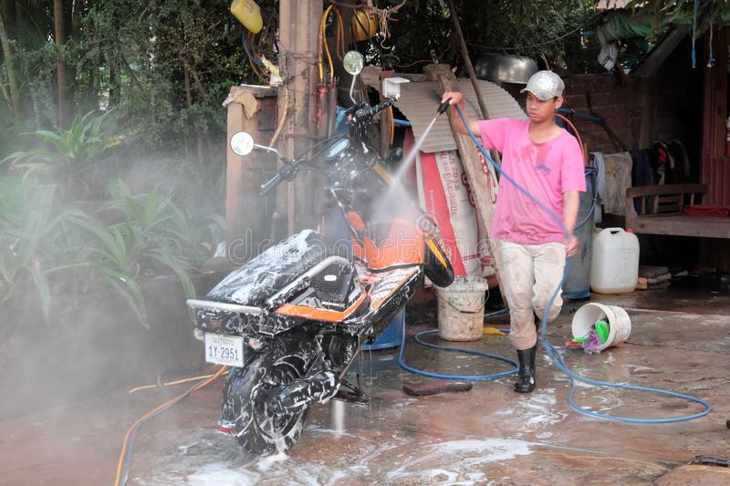 Teenager in a pink t-shirt, cap and rubber boots washes a scooter. Motor scooter in white. Siem Reap, Cambodia, December 17, 2018 teenager in a pink t-shirt, cap royalty free stock photo