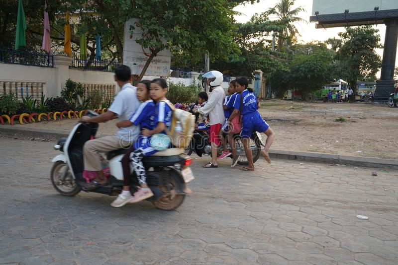 Four persons riding on one motorcycle heading for a school on National Highway 6 in Siem Reap, stock photo