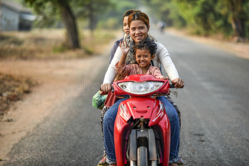 Siem Reap, Cambodia, March 18, 2016: Cambodian girls and children on a scooter smiling and waving royalty free stock photography