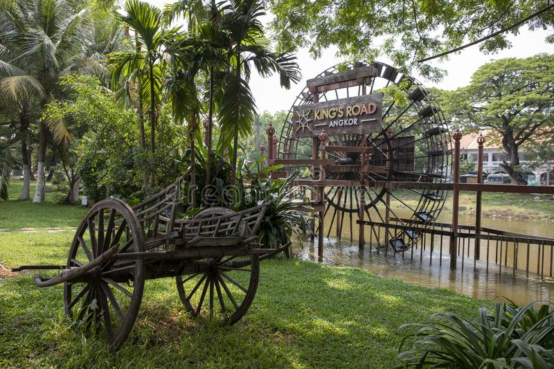 Siem Reap, Cambodia - 27 March 2018: Rustic wooden carriage and water mill wheel. Wooden. Watermill wheel. Traditional khmer village landscape. Old wooden cart stock image