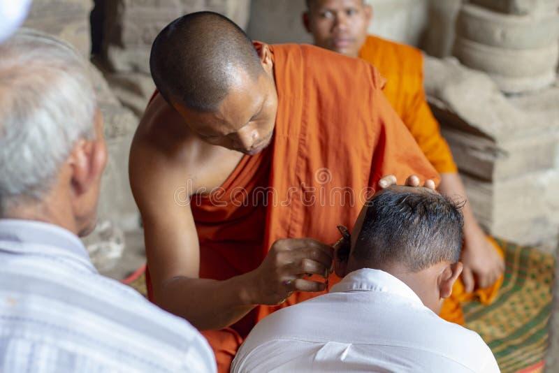 Siem Reap Cambodja - 14 April 2018: ritualer för buddistiska munkar i den Angkor Wat templet Buddist i orange kläder arkivfoto