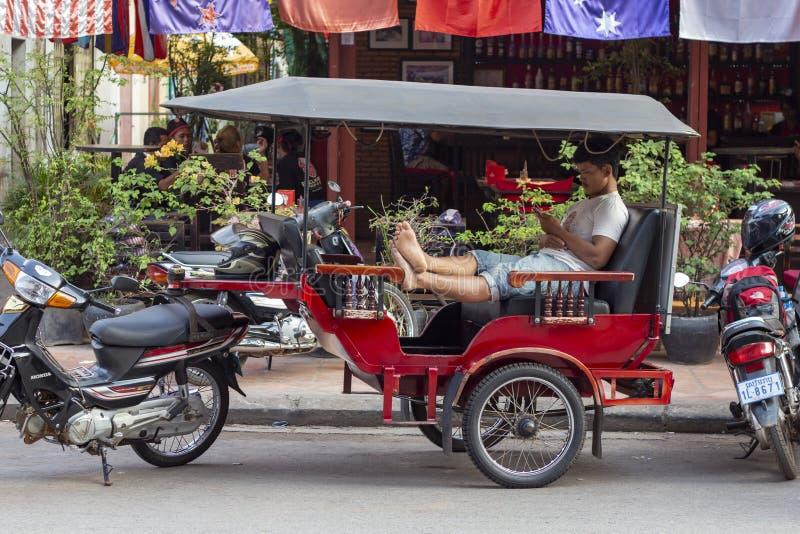 Siem Reap Cambodja - 25 mars 2018: tuk-tukchauffören vilar i passagerarelagledare med mobiltelefonen royaltyfri foto