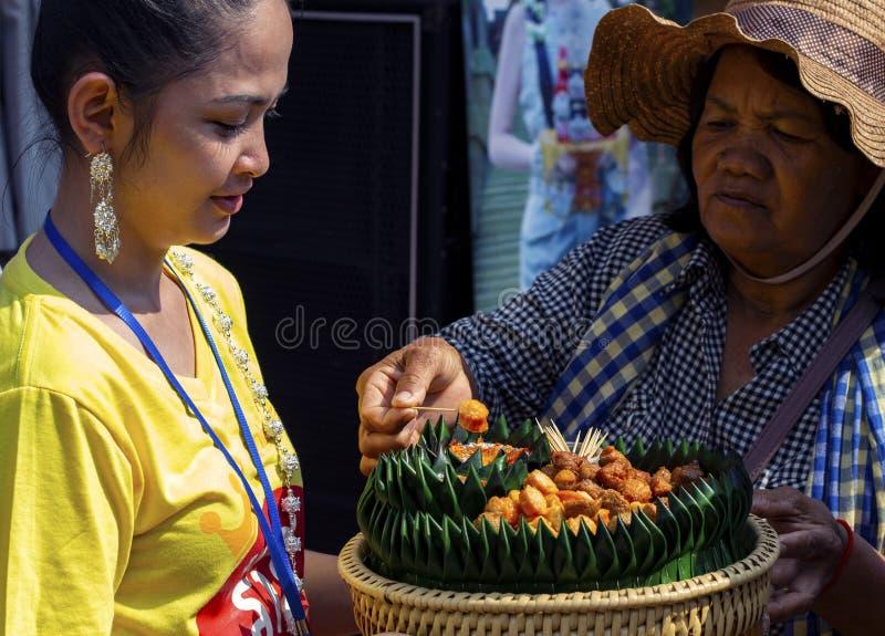 Siem Reap - 14 de abril de 2018: A menina cambojana do promotor dá o alimento para tentar à mulher adulta Canape pequeno do prese imagem de stock royalty free