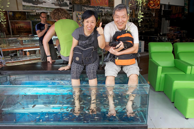 Siem Reap. Fish foot massage for two tourists along the street in Siem Reap, Cambodia. The major focus of fish foot massage is the exfoliation. The idea is that royalty free stock images