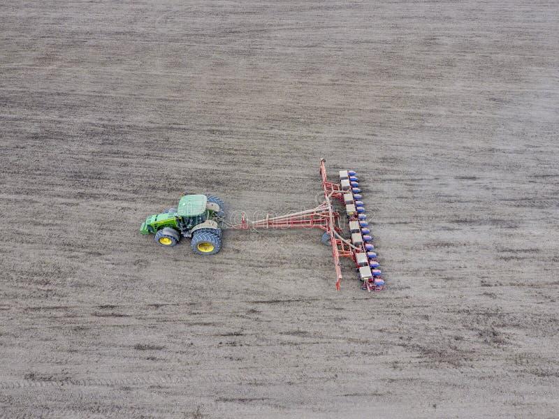Siembra del maíz Tractor con una sembradora en el campo Usando una sembradora para plantar maíz imagen de archivo libre de regalías