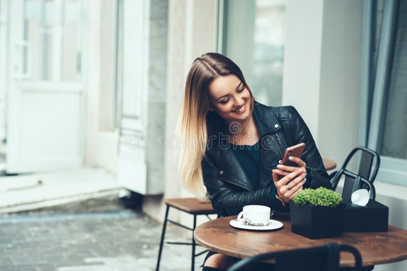 Siempre feliz de comunicar con los amigos Mujer joven hermosa que se sienta en mensaje que mecanografía del café a su amigo mient imagenes de archivo