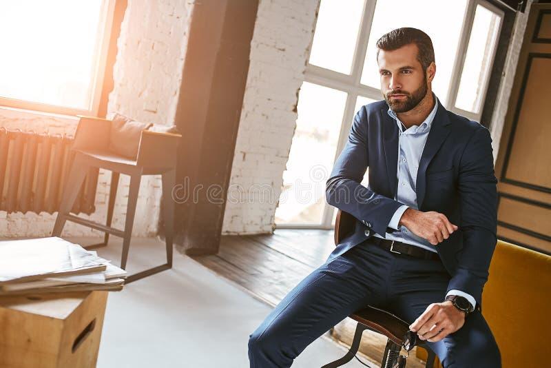 Siempre perfecto Hombre de negocios encantador y agradable y barbudo en el traje elegante que se sienta en butaca y que mira lejo imágenes de archivo libres de regalías