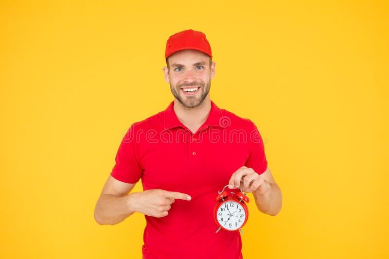 Siempre a tiempo Hombre feliz con el despertador en fondo amarillo Entrega de su compra Suministro de servicios del mensajero fotografía de archivo