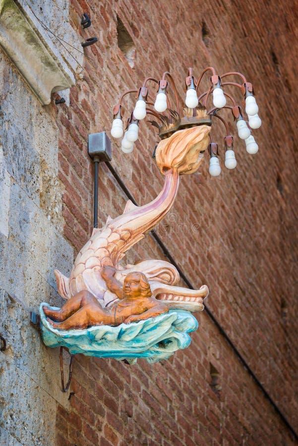 Siena em Toscânia, Itália - um golfinho, emblema do distrito da onda do contrada de Onda em uma rua durante o festival do palio fotos de stock royalty free