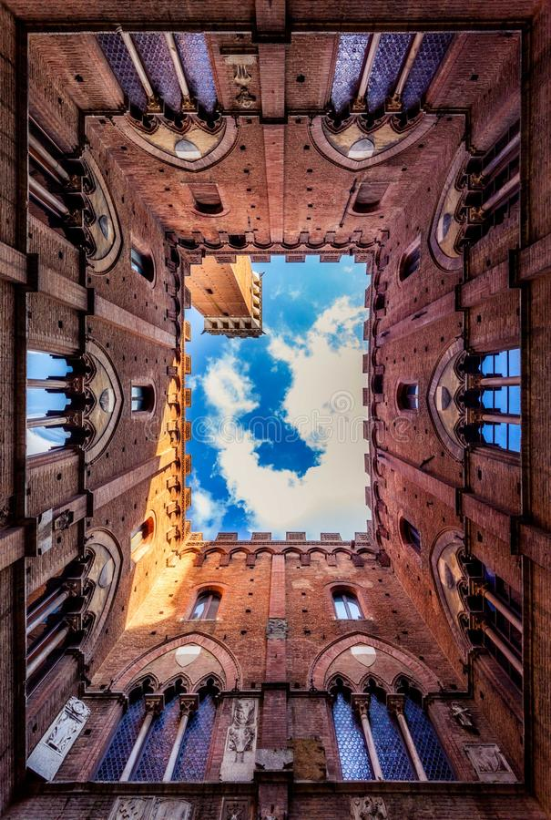Siena Looking Up Tower Castle Courtyard. Siena is an incredible, winding city just packed with tourists and shops and wonderful sights, but not so many people royalty free stock photos