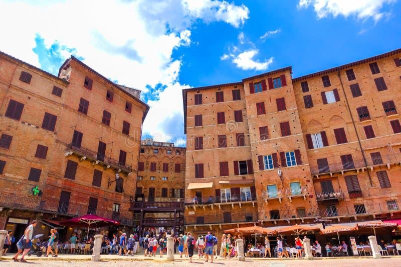 Siena Italien-Juli 4, 2016: Kafé och restauranger med lotten av turister på Piazza del Campo arkivbild