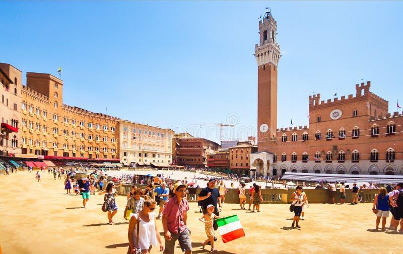 Siena Italien - Juli 2, 2012: Turister och lokalt folk som samlar på Piazza del Campo nära Torre del Mangia för att hålla ögonen  royaltyfria bilder