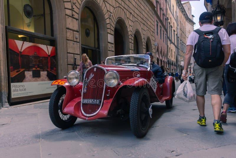 Siena Italien - Maj 18, 2018 Gammal röd racerbil på gatorna av staden av Siena under loppet av tusen mil på Maj 18, royaltyfria foton