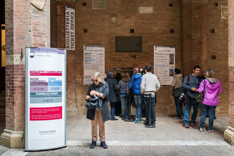 Queue to purchase a ticket at the ticket office to visit the Palazzo Pubblico in Siena, Italy. Siena, Italy - October 29th, 2017: Queue to purchase a ticket at royalty free stock photos