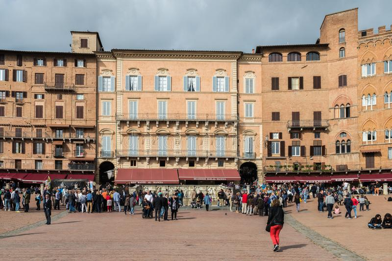 Piazza del Campo and Palazzo Pubblico in Siena, Tuscany. Siena, Tuscany - October 29th, 2017: Medieval Piazza del Campo and Palazzo Pubblico in Siena, Tuscany royalty free stock photo