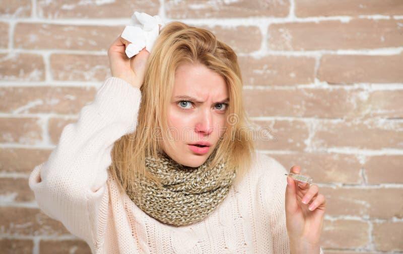 Siendo febril Mujer enferma que sostiene el termómetro de la fiebre El llegar a ser mal con frío o gripe Cuerpo de medición de la fotografía de archivo libre de regalías