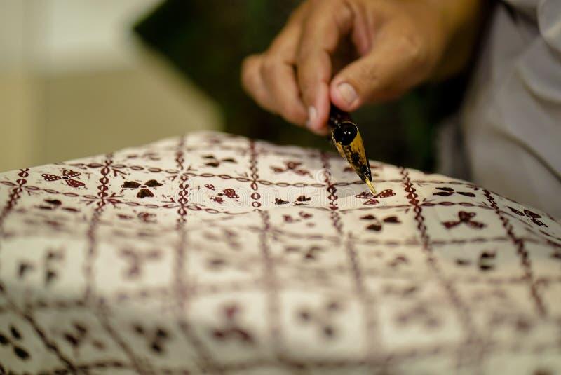 Sierpień 11 2019, Surakarta Indonezja: Zamyka W górę ręki robić batikowi na tkaninie z canting z bokeh tłem obrazy royalty free
