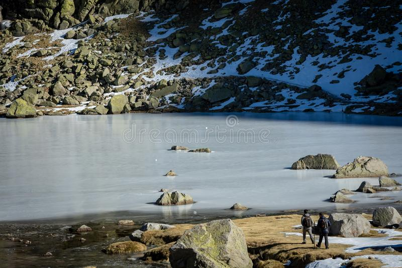 Sierra DE Gredos, Spanje 12-januari-2019 Twee trekkers die op de sneeuw naar een bevroren meer tijdens een mooie de winterdag lop stock foto