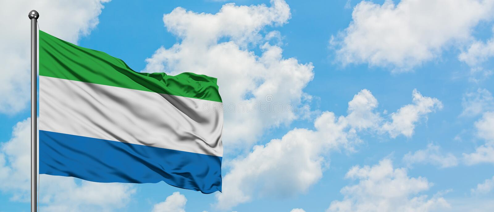 Sierra Leone flag waving in the wind against white cloudy blue sky. Diplomacy concept, international relations.  royalty free stock photo