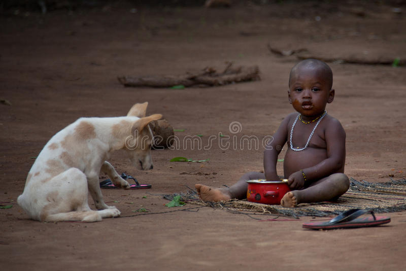 Sierra Leone, West Africa, the beaches of Yongoro. Yongoro, Sierra Leone - June 03, 2013: West Africa, the village of Yongoro in front of Freetown, child and dog stock image