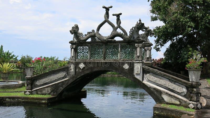 Siersteenbrug over waterkanaal in koninklijke tuin De historische bouw met elementen van Balinese cultuur royalty-vrije stock fotografie