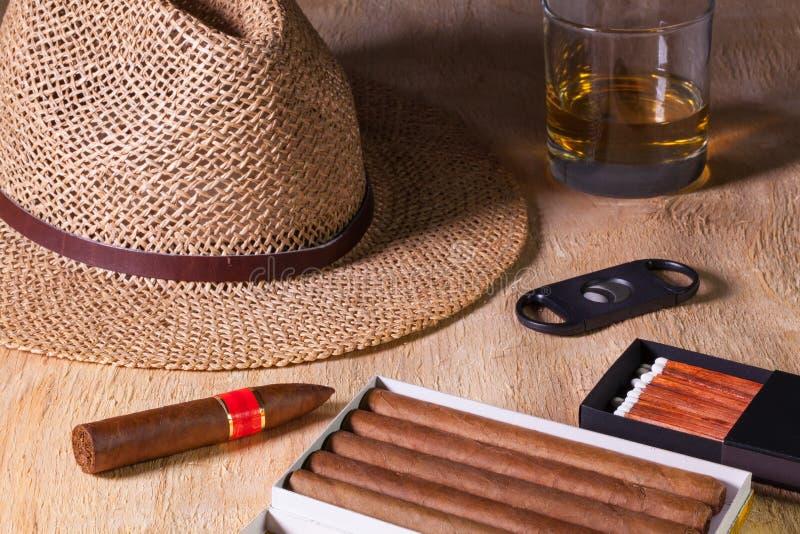 Siesta - sigari, cappello di paglia e whiskey scozzese su uno scrittorio di legno immagine stock libera da diritti