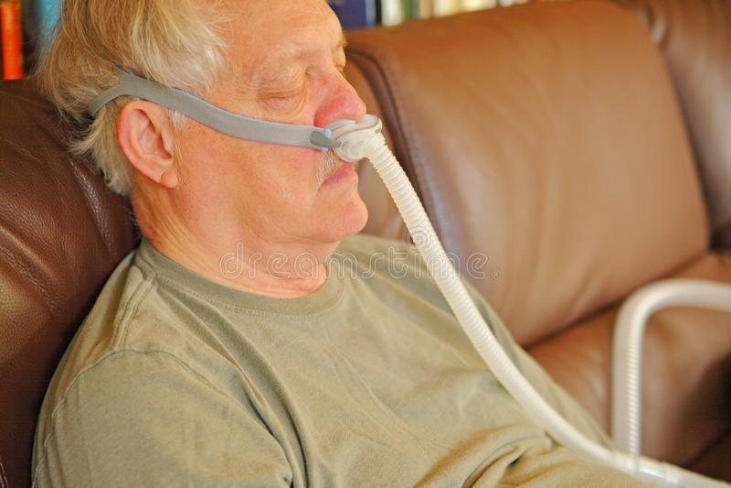 Siestas del hombre mayor con el dispositivo de CPAP foto de archivo