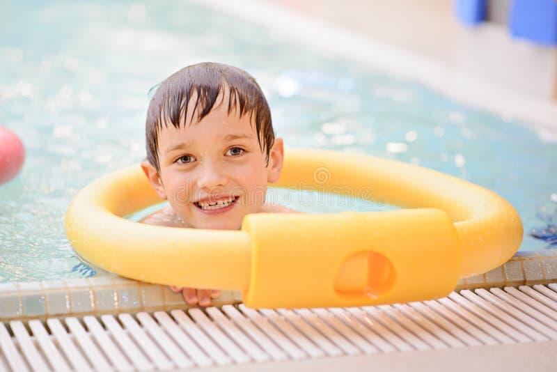 Siete años del muchacho que aprende nadar en la piscina imagenes de archivo
